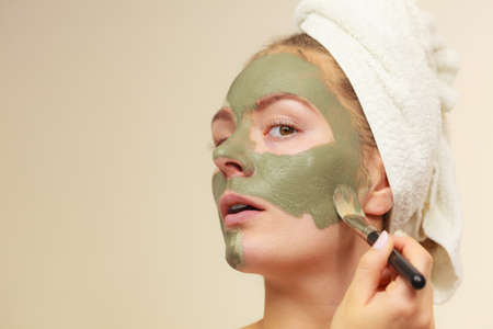 purifying: Skin care. Woman applying with brush clay mud mask to her face. Girl taking care of oily complexion. Beauty treatment.