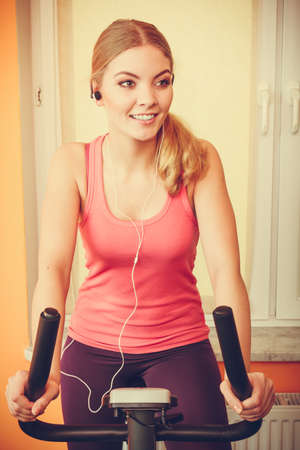 active listening: Active young woman working out on exercise bike stationary bicycle. Sporty girl training at home listening music. Fitness and weight loss concept. Instagram filtered. Stock Photo