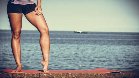vitaly: Sports and activities. Part body of training active sporty girl outside. Slim fit legs on seaside. Stock Photo