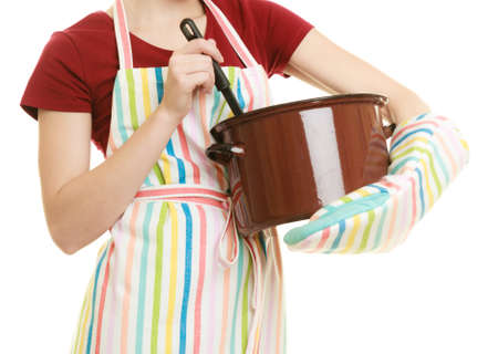 stereotypical: Happy housewife or chef in colorful kitchen apron with pot of soup and ladle isolated studio shot