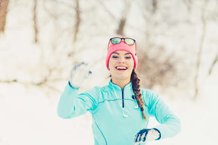 snowballs: Girl has fun throwing snowballs. Relax in winter park. Health nature fitness fashion concept.