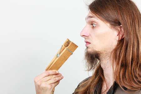 olfato: El hombre con el clip de pinza de la ropa clavija en la nariz. Joven chico de pelo largo sentirse mal olor desagradable olor. Concepto de mal olor. Foto de archivo