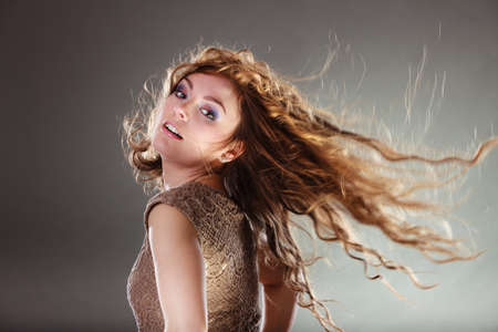 intriguing: Mysterious enigmatic woman in studio on grey. Young intriguing attractive girl with flying long curly hair in motion. Shining light. Stock Photo