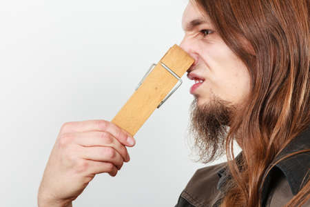 unpleasant smell: Man with clothespin clip peg on his nose. Young long haired guy feeling unpleasant odor stink. Bad smell concept.