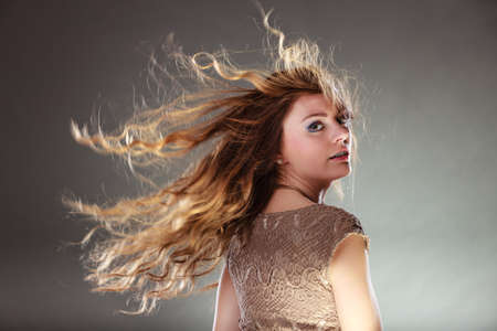 intriguing: Portrait of mysterious enigmatic woman. Young intriguing attractive girl with flying hair in motion. Shining light. Stock Photo