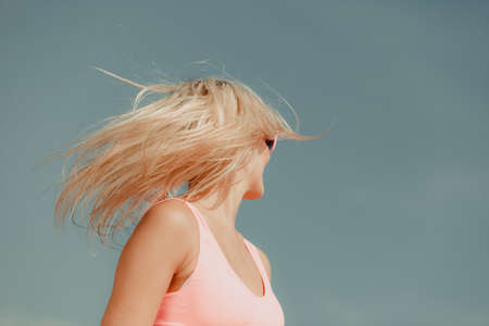 crazy hair: Young blonde pretty girl on beach. Woman wearing sunglasses have active time in summer with crazy hair. Summertime concept copy space.