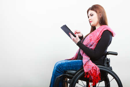 university life: College university and job concept. Mobile technology. Young student worker woman with tablet ebook on wheelchair. Disabled person in real life.