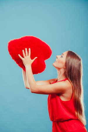 throw cushion: Pretty cute young woman girl throwing red heart shape pillow in studio on blue. Valentines day love. Stock Photo