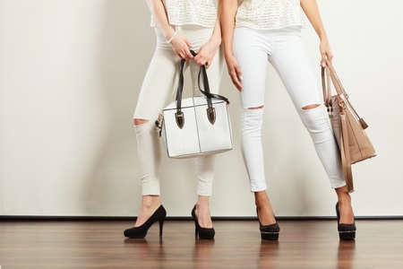 Mode-accessoires voor vrouwen. Twee dames houden van handtassen. Meisjes dragen witte broek en zwarte hoge hakken.