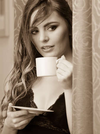 energizing: Sensual seductive woman in lingerie drinking cup of coffee by curtain at home. Young girl with hot energizing beverage stay awake. Caffeine energy. Black and white.