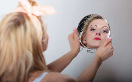 hairband: pin up beautiful blonde fashion girl in hairband looking at the mirror retro styling , studio shot gray background Stock Photo