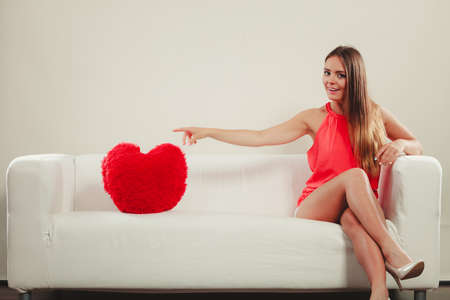 picking fingers: Pretty cute young woman girl with red heart shape pillow sitting on white sofa couch. Valentines day love.