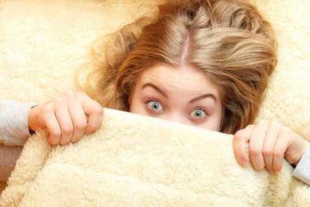 rested: Woman waking up in bed in the morning after sleeping. Well rested young girl laying covering face with wool woolen blanket. Stock Photo
