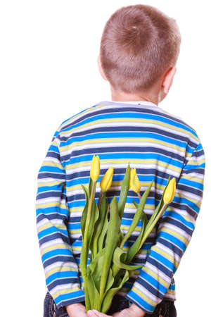 gift behind back: Special occasions holiday and mother day. Young boy prepare surprise gift flowers hold tulips behind back.