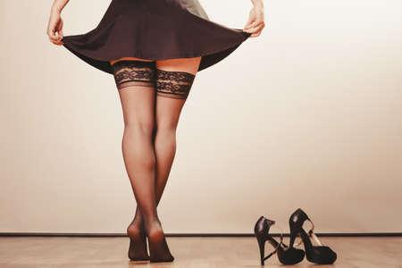 sexualidad: Belleza y la sexualidad de las mujeres. Modelo de la mujer parte del cuerpo que desgasta atractivo negro de la falda del vestido y pantalones medias. Piernas femeninas con tacones altos.
