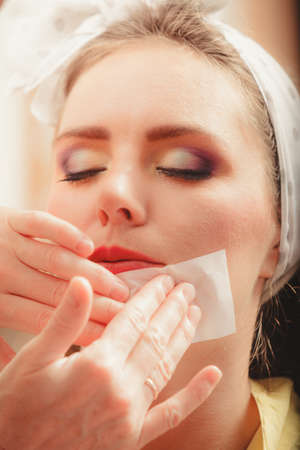 visagiste: Make up artist using oil absorbing tissues sheets. Closeup of visagiste and pretty young woman girl. Beauty and makeup concept.