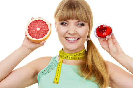 deciding: Woman with measuring tape holds in hands cake and grapefruit choosing, deciding between sweet food or fresh fruit, make dietary choice. Weight loss diet dilemma concept. Isolated on white