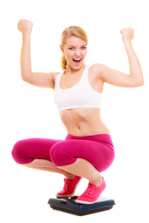 weight loss success: Dieting weight loss success. Happy joyful young woman girl on weighing scale raising her arms hands. Healthy lifestyle concept. Isolated on white background. Stock Photo