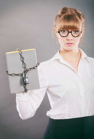 Businesswoman holding document file chained with padlock. Confidential secret data.
