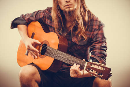 oldschool: Sitting long haired bearded man playing guitar. Young male creating music. Instrument passion hobby oldschool concept.