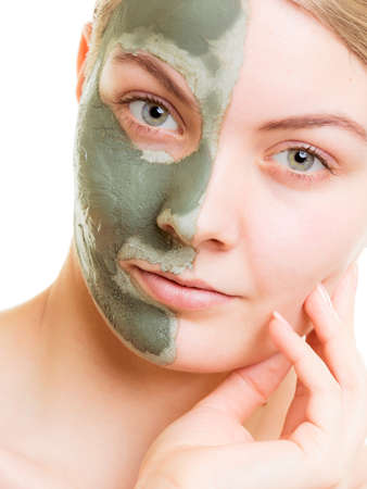 complexion: Skin care. Woman in clay mud mask on face isolated on white. Girl taking care of dry complexion. Beauty treatment. Stock Photo