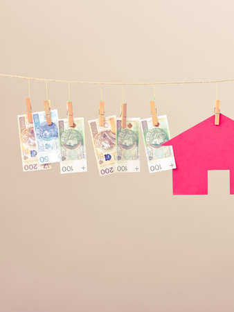 laundry line: Red house with banknotes cash hang on laundry line. Selling and buying home concept. Stock Photo