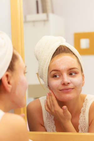 layer mask: Woman applying mask moisturizing skin cream on face looking in bathroom mirror. Girl taking care of her complexion layering moisturizer. Skincare spa treatment.