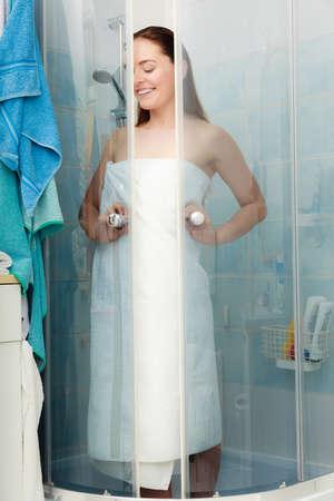 cabine de douche: Fille douche dans une cabine de douche cabine enceinte. Jeune femme avec une serviette blanche en prenant soin de l'hygi�ne dans la salle.