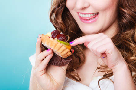 finger licking: Bakery, sweet food and people concept. Closeup smiling cute woman curly hair holding fruit cake cupcake in hand on blue Stock Photo