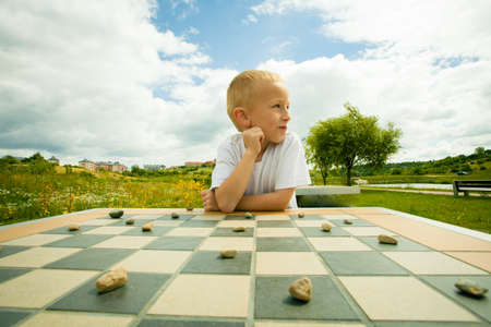 draughts: Draughts board game. Little boy clever child kid playing checkers thinking, outdoor in the park. Childhood and development