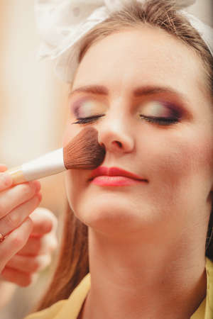 visagiste: Make up artist applying makeup using brush on pretty gorgeous woman. Closeup of visagiste and young girl. Beauty and makeup concept. Stock Photo