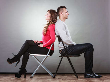 impasse: Bad relationship concept. Man and woman in disagreement. Young couple after quarrel sitting on chairs back to back Stock Photo