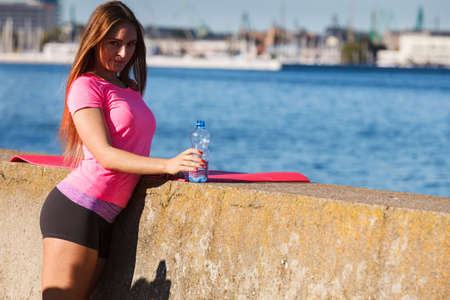 thirst: Woman in sportswear takes a break to rehydrate drinking water from plastic bottle, resting after sport workout outdoor by seaside