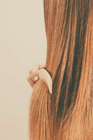 combing: Woman combing brushing her long smooth hair close up. Girl taking care refreshing her hairstyle. Haircare concept. Stock Photo