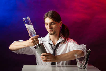 bartending: Entertainment alcohol bartending concept. Bartender pouring liquor into glass. Young tapster making a drink.