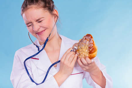 dietitian: Disgusted dietitian nutritionist checking examine sweet roll bun with stethoscope. Woman with fattening junk food. Bad unhealthy eating nutrition concept. Stock Photo