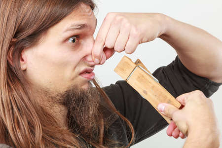 unpleasant smell: Unpleasant bad smell concept. Portrait of young long haired man with clogged nose by big clothespin.
