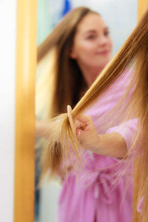 bad hygiene: Woman combing brushing her long smooth hair in bathroom, looking in mirror. Girl taking care refreshing her hairstyle. Haircare concept. Stock Photo