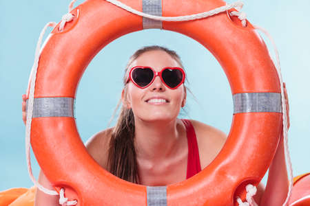 savers: Happy woman girl in heart shape sunglasses with ring buoy lifebuoy.