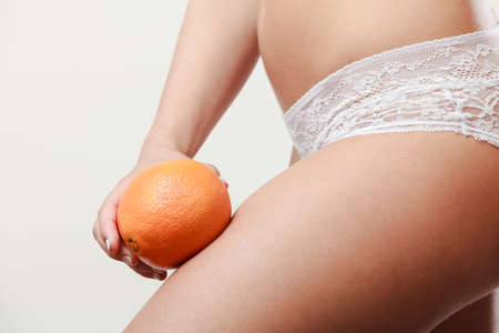 with orange and white body: Absence of cellulite. Part body of slim fit girl holding orange next to the leg  Woman wearing white lacy lingerie. Diet aspects.