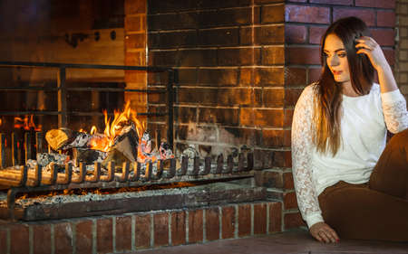nostalgic: Melancholic pensive woman relaxing resting at fireplace. Thoughtful nostalgic young girl heating warming up. Winter at home. Stock Photo
