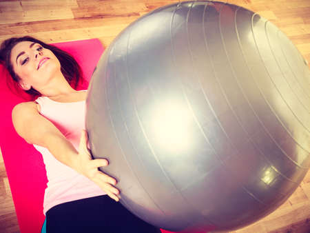 fit ball: Sport, fitness, people, gym concept. Young lady lying on mat with fit ball. Girl is doing workout.
