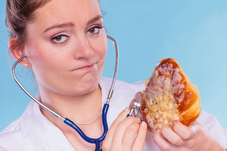 disgusted: Disgusted dietitian nutritionist checking examine sweet roll bun with stethoscope. Woman with fattening junk food. Bad unhealthy eating nutrition concept. Stock Photo