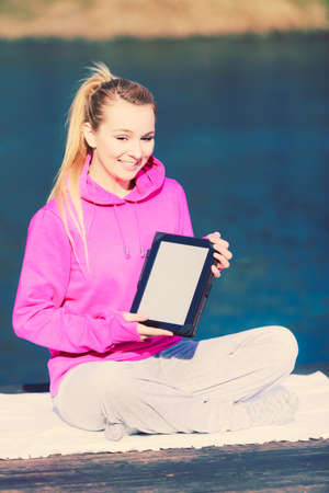 display figure: Young girl sitting in park learning yoga from tablet display screen. Taking care about healthy lifestyle and slim figure. Sport with technology.