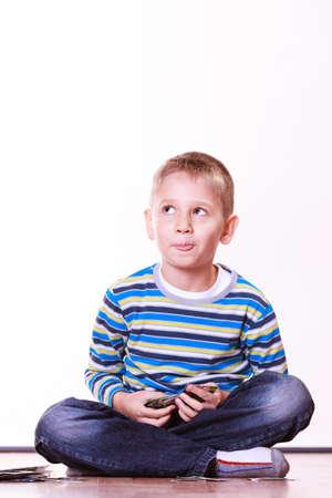 recoger: tiempo libre, diversión y pasatiempo. Juego del niño pequeño en el interior sentarse en el piso y jugar recoger las cartas.