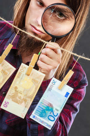 laundry line: Currency exchange concept. Man worker check verify money cash. Payment hang on laundry line. Guy with loupe.