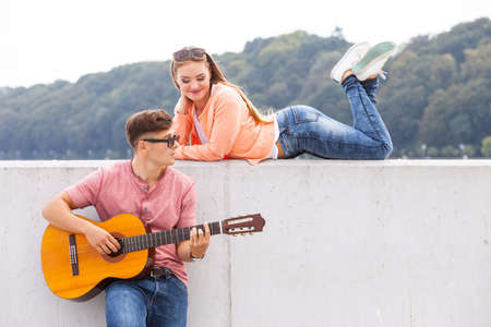 muse: Love romance music talent passion dating concept. Guitarist and his muse. Young man playing guitar with girl lying on wall with scenery background.