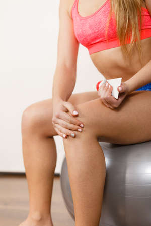 ointment: Woman fitness girl sitting on fit ball putting ointment cream on bad injured knee. Sport training gym and health care