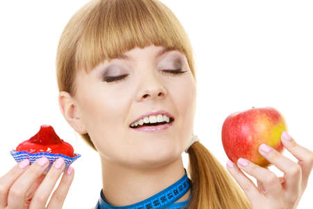 chose: Woman with measuring tape holds in hand cake and apple fruit choosing, trying to resist temptation, make the right dietary choice. Weight loss diet dilemma gluttony concept. Isolated on white