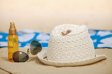 sun oil: Summer vacations concept. Beach accessories. Straw hat sunglasses sun oil and blanket on sand. Stock Photo